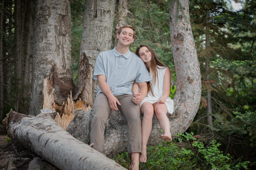 A happy couple is sitting on a tree